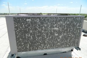 Rooftop air conditioning unit with hail damage.